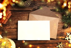 Flat lay composition with blank Christmas card on wooden table. Space for text