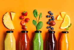 Flat lay composition with bottles of delicious juices and fresh ingredients on orange background