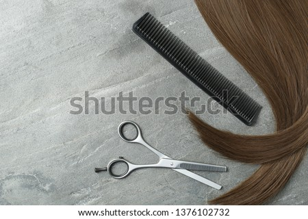 Flat lay composition with brown hair, comb, thinning scissors and space for text on grey background. Hairdresser service