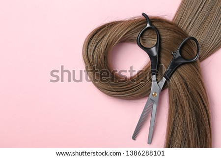 Flat lay composition with brown hair, thinning scissors and space for text on color background. Hairdresser service