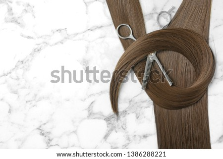 Flat lay composition with brown hair, thinning scissors and space for text on marble background. Hairdresser service