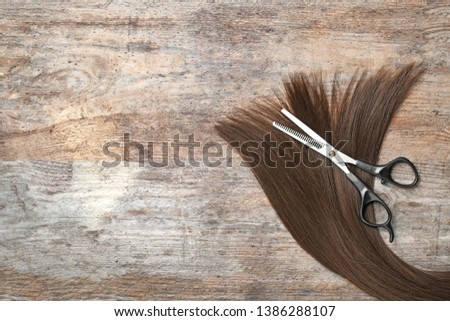 Flat lay composition with brown hair, thinning scissors and space for text on wooden background. Hairdresser service