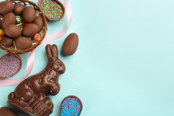 Flat lay composition with chocolate Easter bunny, eggs and candies on light blue background. Space for text
