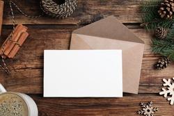 Flat lay composition with Christmas decor and blank card on wooden background. Space for text