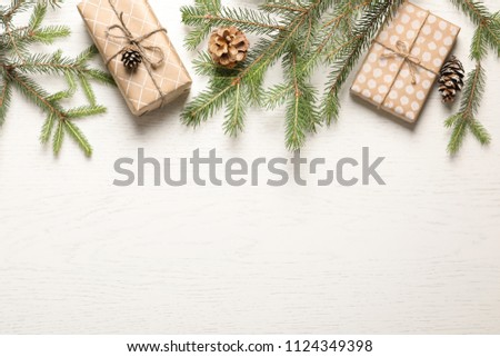 Flat lay composition with Christmas gifts and fir branches on light background #1124349398