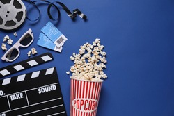 Flat lay composition with clapperboard, cinema tickets and 3d glasses on blue background, space for text