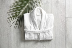 Flat lay composition with clean folded bathrobe on light wooden background