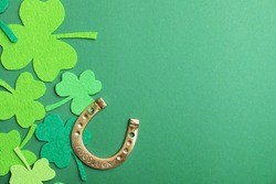 Flat lay composition with clover leaves and horseshoe on green background, space for text. St. Patrick's day