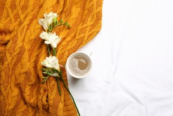 Flat lay composition with coffee and warm plaid on white bedsheet, space for text