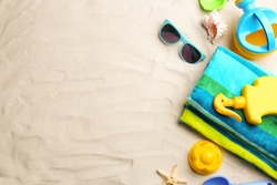 Flat lay composition with colorful beach toys on sand. Space for text