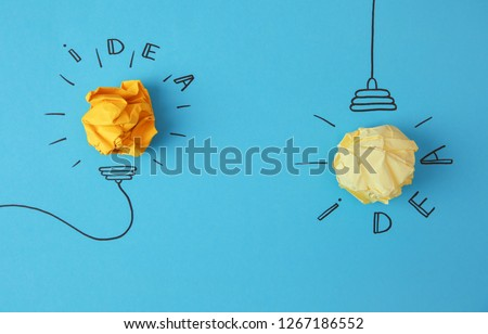 Flat lay composition with crumpled paper as lamp bulbs and words IDEA on color background #1267186552