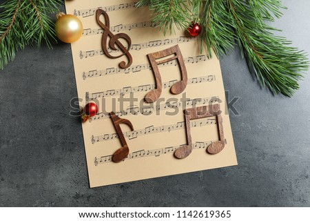 Flat lay composition with decoration and music sheet on table. Christmas songs concept