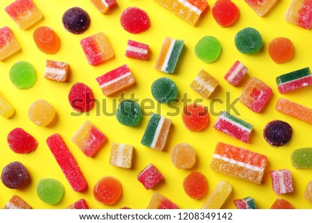 Flat lay composition with delicious colorful candies on color background