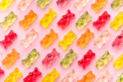 Flat lay composition with delicious jelly bears, jelly bears pattern on pink background