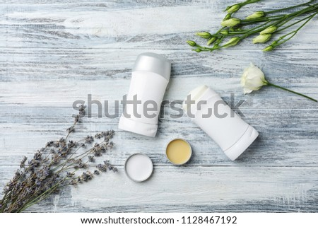 Flat lay composition with different deodorants and flowers on wooden background