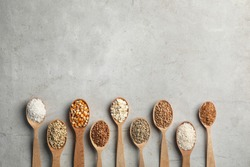 Flat lay composition with different types of grains and cereals on grey background