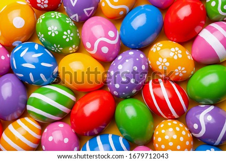 Flat lay composition with Easter eggs on color background. Pattern made of decorated eggs. Top view