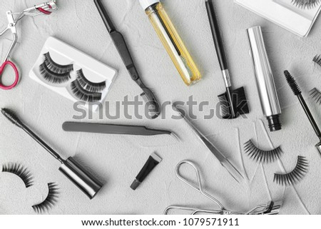 Flat lay composition with false eyelashes, cosmetic products and tools on grey background