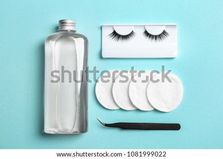 Flat lay composition with false eyelashes, lotion and tweezers on color background