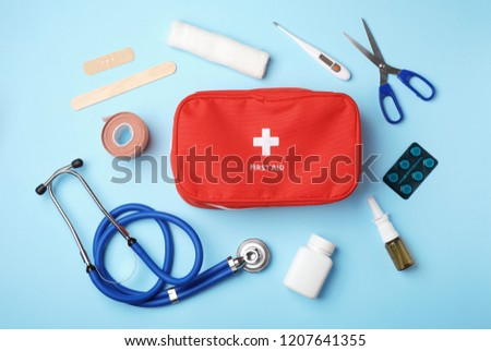 Flat lay composition with first aid kit on color background