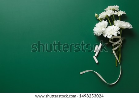 Flat lay composition with flowers on green chalkboard, space for text. Teacher's day