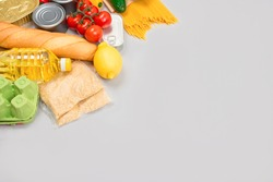 Flat lay composition with food donations on grey background with copyspace - pasta, fresh vegatables, canned food, baguette, cooking oil. Food donations and food bank concept