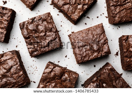 Flat lay composition with fresh brownies on parchment paper. Delicious chocolate pie #1406785433