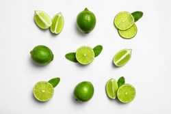 Flat lay composition with fresh juicy limes and mint on white background