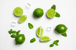 Flat lay composition with fresh juicy limes, mint and ice cubes on white background