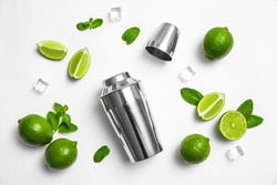 Flat lay composition with fresh juicy limes, mint, ice cubes and cocktail shaker on white background