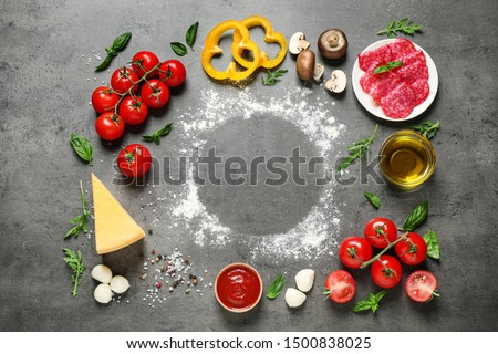 Flat lay composition with fresh pizza ingredients on grey table, space for text