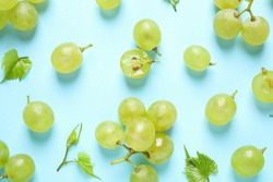 Flat lay composition with fresh ripe juicy grapes on light blue background