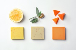 Flat lay composition with handmade soap bars and ingredients on white background