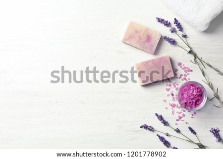 Flat lay composition with handmade soap bars and space for text on white wooden background
