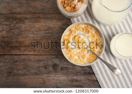 Flat lay composition with healthy cornflakes and milk in bowl on wooden table. Space for text #1208317000
