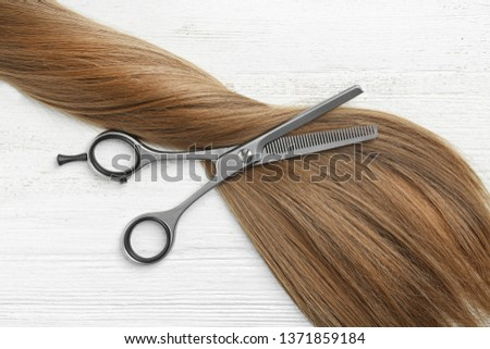 Flat lay composition with light brown hair and thinning scissors on white wooden background. Hairdresser service