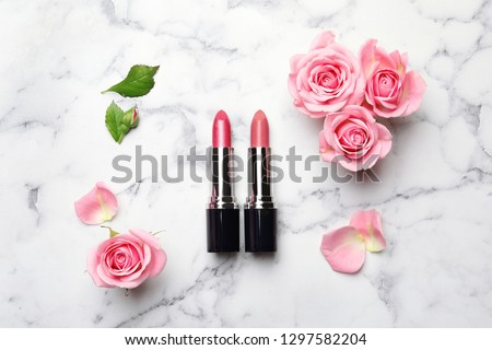 Flat lay composition with lipsticks and roses on marble background