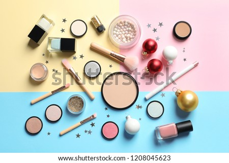 Flat lay composition with makeup products and Christmas decor on color background