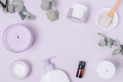 Flat lay composition with natural cosmetics for face and body, moisturizer cream, clay and essential oil next to candles and eucalyptus leaves on lilac background with empty space in the center