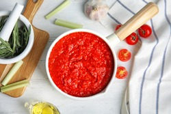 Flat lay composition with pan of tomato sauce on white wooden table