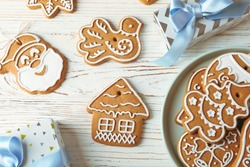Flat lay composition with plate of Christmas cookies, gift boxes on white wooden background. Top view