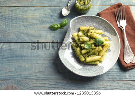Flat lay composition with plate of delicious basil pesto pasta and space for text on wooden table #1235015356