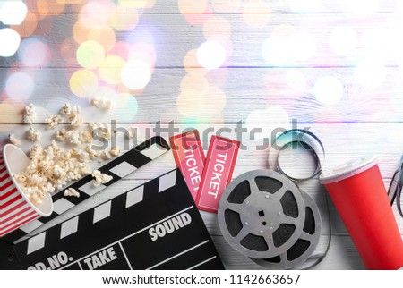 Flat lay composition with popcorn, filmstrips and blurred lights on wooden background. Cinema evening