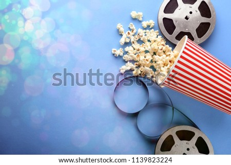Flat lay composition with popcorn, filmstrips and space for text on color background. Cinema evening
