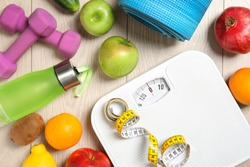 Flat lay composition with scales, healthy food and sport equipment on wooden background. Weight loss
