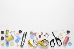 Flat lay composition with scissors and sewing supplies on white background. Space for text