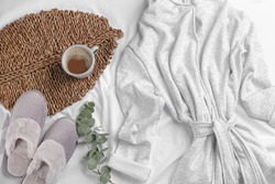 Flat lay composition with slippers and bath robe on white bedsheet. Comfortable home outfit