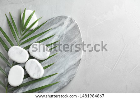 Flat lay composition with spa stones and palm leaf on grey table, space for text