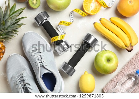 Flat lay composition with sport items and healthy food on grey background. Weight loss concept