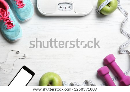 Flat lay composition with sport items, scales and space for text on wooden background. Weight loss concept #1258391809
